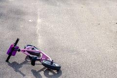 Bicicleta rosada solitaria después del accidente en la calle imagenes de archivo