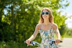 Bicicleta sonriente feliz del montar a caballo de la mujer joven en verano Imagenes de archivo