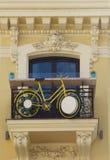 Bicicleta suspendida en el balcón del un edificio viejo Imágenes de archivo libres de regalías