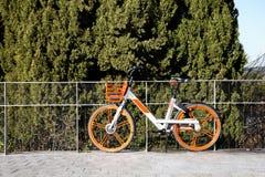 Bicicleta urbana alaranjada para o aluguel na cidade de madrid foto de stock