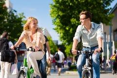 Bicicleta urbana da equitação dos pares no tempo livre na cidade Fotografia de Stock