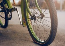 A bicicleta verde, estando no asfalto com um pneu liso imagens de stock