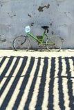 Bicicleta verde na areia na parede velha fotografia de stock