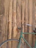 Bicicleta verde oxidada del viejo estilo y pared de madera Fotos de archivo