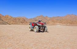 Bicicleta vermelha do quadrilátero no deserto Fotografia de Stock Royalty Free