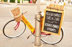 A bicicleta vermelha na frente do mercado das rochas em Sydney mostra o ` sábado e domingo das horas de troca, mercado do foodie  Foto de Stock Royalty Free