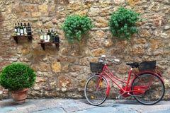 Bicicleta vermelha que está na frente da parede de pedra na cidade antiga italiana toscânia Pienza Imagem de Stock