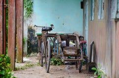 Bicicleta vieja del vintage con el carro metálico delante de una casa vieja abandonada deteriorada Foto de archivo