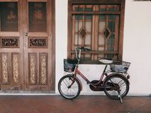 Bicicleta vieja delante de la casa vieja de Asia Foto de archivo libre de regalías