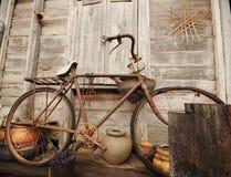Bicicleta vieja y casa de madera vieja Fotografía de archivo