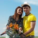 Bicicleta y pares felices que se divierten al aire libre Fotos de archivo libres de regalías