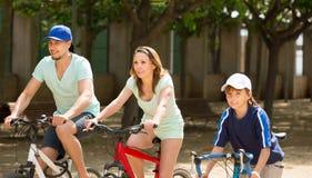 Bicicletas americanas da equitação da família na unidade do parque Imagens de Stock