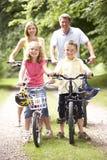 Bicicletas da equitação da família no campo Imagens de Stock Royalty Free