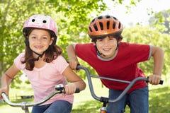 Bicicletas da equitação do menino e da menina fotografia de stock