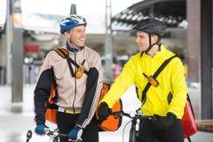 Bicicletas de Delivery Men With del mensajero que miran cada uno Imagen de archivo libre de regalías