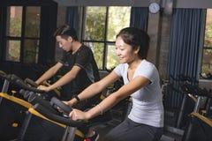 Bicicletas de exercício asiáticas do ciclismo do homem no gym Imagem de Stock