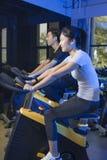 Bicicletas de exercício asiáticas do ciclismo do homem no gym Imagens de Stock Royalty Free
