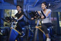 Bicicletas de exercício asiáticas do homem no gym Foto de Stock Royalty Free