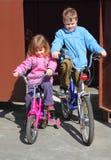 Bicicletas de los niños del paseo del hermano y de la hermana imagenes de archivo
