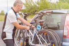 Bicicletas del cargamento del hombre en el estante de la bici Imágenes de archivo libres de regalías