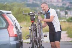 Bicicletas del cargamento del hombre en el estante de la bici Foto de archivo libre de regalías
