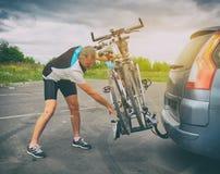 Bicicletas del cargamento del hombre en el estante de la bici fotos de archivo libres de regalías