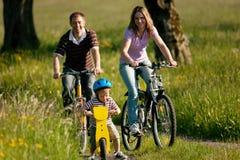 Bicicletas del montar a caballo de la familia en verano Foto de archivo