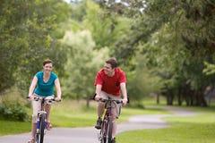 Bicicletas del montar a caballo de los pares en el parque - horizontal Imagenes de archivo