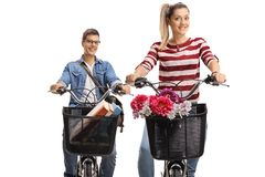 Bicicletas do homem novo e de uma equitação da jovem mulher Fotos de Stock