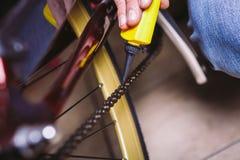 Bicicletas do reparo do tema Close-up de um uso caucasiano da mão do ` s do homem um lubrificante Chain em um lubrificador amarel foto de stock