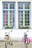 Bicicletas e casa branca com janelas azuis Fotografia de Stock Royalty Free