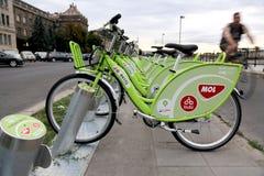 Bicicletas em uma estação de ancoragem departilha pública dos sistemas Um homem está dando um ciclo no fundo Imagens de Stock Royalty Free