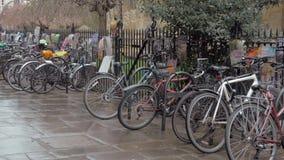 Bicicletas estacionadas contra os trilhos com muitos cartazes nele video estoque