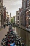 Bicicletas estacionadas contra um canal em Amsterdão Fotografia de Stock Royalty Free