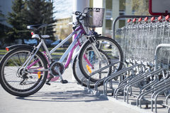 Bicicletas estacionadas em uma cremalheira parcking na frente do supermercado Fotografia de Stock Royalty Free