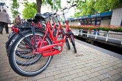 Bicicletas estacionadas pelo canal em Amsterdão Fotografia de Stock