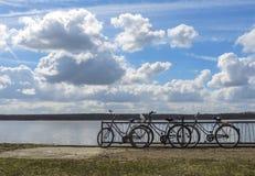 3 bicicletas estacionaram ao lado do lago em um dia claro contudo nebuloso do outono imagens de stock