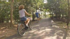 Bicicletas felices jovenes del montar a caballo de los pares del inconformista en el parque con el perro casero que corre cerca H almacen de metraje de vídeo