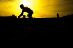 Bicicletas fora contra o por do sol Fotos de Stock