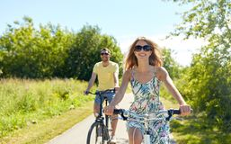 Bicicletas jovenes felices del montar a caballo de los pares en verano fotos de archivo libres de regalías