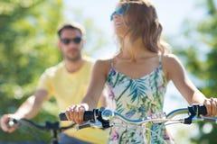 Bicicletas jovenes felices del montar a caballo de los pares en verano imagen de archivo