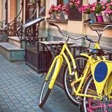 Bicicletas no estacionamento perto do café com flores Imagens de Stock