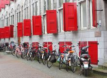 Bicicletas perto de uma construção antiga com abrigos e as janelas de vitral vermelhos, Utrecht, Países Baixos Fotos de Stock