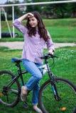 Bicicletas que dão um ciclo a menina A menina monta a cidade da bicicleta para fora fotografia de stock royalty free