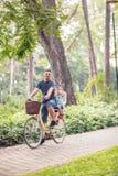 Bicicletas que montan sonrientes del papá y del hijo al aire libre en un parque de la ciudad foto de archivo libre de regalías