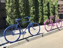 Bicicletas velhas custadas como uma cerca da estrada Pintado em cores diferentes Fotos de Stock
