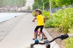 Bicicletta africana di guida della ragazza sul vicolo del ciclo in città Immagine Stock