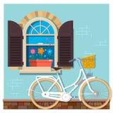 Bicicletta bianca vicino alla facciata della costruzione con una finestra Facciata della costruzione della via della casa con la  Immagine Stock