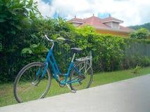 Bicicletta blu a sinistra che sta lungo una strada in un sobborgo di Victoria Fotografia Stock
