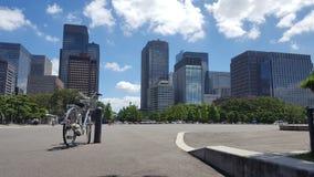 bicicletta con costruzione ed il chiaro cielo Fotografie Stock Libere da Diritti